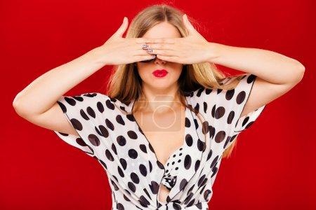 Photo pour Jeune belle femme, vêtue d'une blouse blanche et d'un soutien-gorge à pois noirs et de lunettes de soleil, fermant les yeux par ses mains, sur fond rouge, en studio, taille haute - image libre de droit