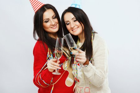 Pretty twins holding glasses with champagne