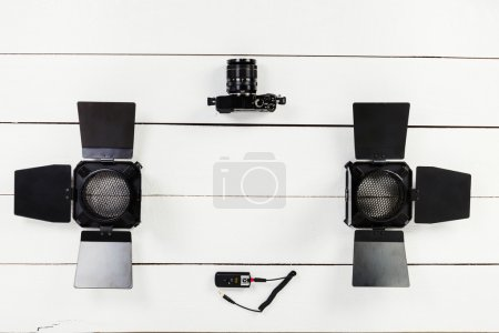 Camera, two barn doors and reflector on table