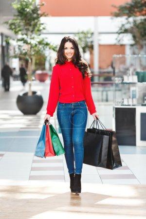 Photo pour Fille debout dans le centre commercial, regardant la caméra et souriant. Belle fille tenant des sacs à provisions colorés dans les deux mains. Porter une blouse rouge, un jean et des chaussures noires. Intérieur, corps entier - image libre de droit