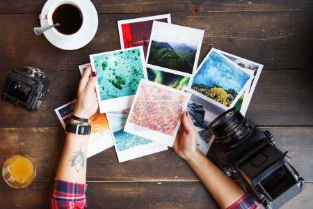 Woman's hands holding printed photos