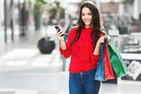 Photo pour Fille debout dans le centre commercial, regardant la caméra et souriant. Belle fille tenant des sacs à provisions colorés dans une main et téléphone dans l'autre main. Les deux mains levées. Porter une blouse rouge et un jean . - image libre de droit