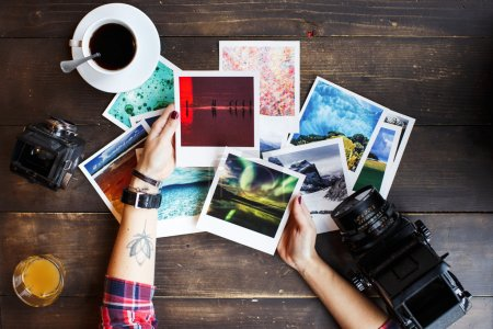 Photo for Women's hands holding printed photos. Dressed in red shirt, lotus tattoo on arm. On old wooden table scattered photos, two old medium format film camera, glass of juice, cup of coffee. Point of view - Royalty Free Image