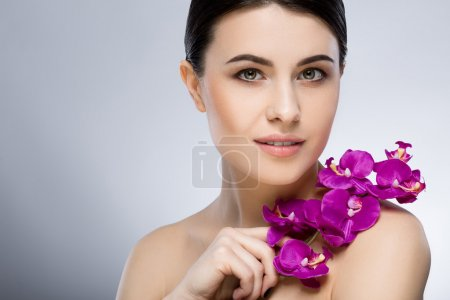 Beautiful girl with naked shoulders holding flower