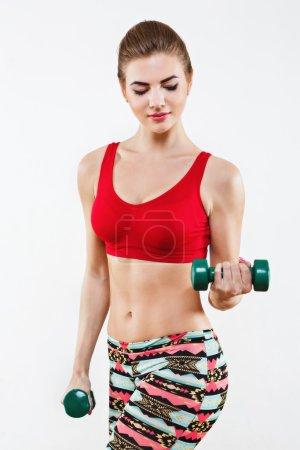 Photo pour Jeune fille aux cheveux brun clair portant des leggings colorés et haut court rouge debout à la salle de gym et faisant des exercices avec haltères vertes, fitness . - image libre de droit