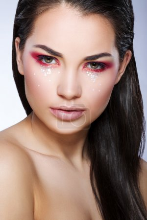 Beautiful model with little glittering stars on face