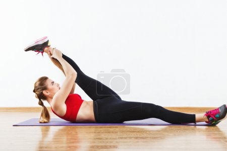 Attractive fit girl doing physical exercises at gym
