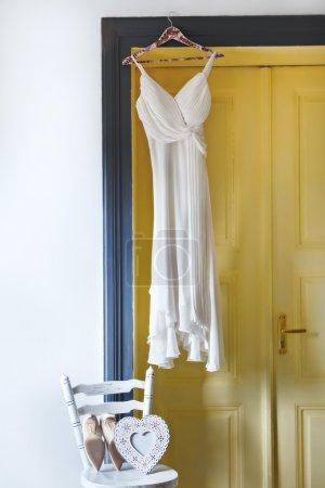 White dress hanging on peg