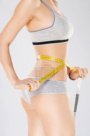 Holding yellow measuring tape on waist