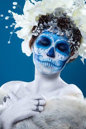 Photo pour Bleu Santa Muerte composent. Jeune femme avec les cheveux court bouclés et visage créatif. Fleurs blanches en cheveux, maquillage, portrait à fond bleu, porte manteau de fourrure. - image libre de droit