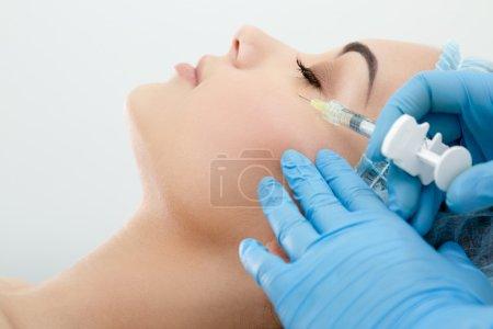 Photo pour Syringe avec remplissage pour le contour du visage ou l'augmentation. Modèle avec les yeux fermés, profil, gros plan. Clinique cosmétologique. Soins de santé, cosmétologie - image libre de droit