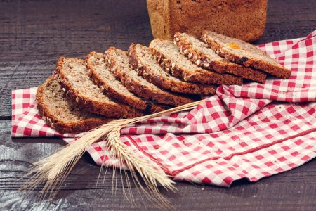 Slices of bread with spikelet of wheat on a cloth on a boards