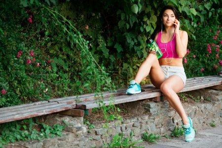Photo pour Fille sportive, aux cheveux longs foncés, vêtue de vêtements de sport, reposant sur un banc après une longue séance d'entraînement, tenant une bouteille dans la main et parlant au téléphone, dans le parc vert, corps entier - image libre de droit