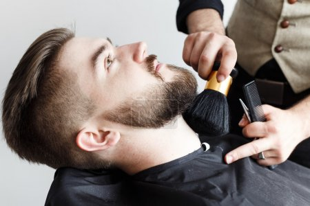 Barber cleaning face of his customer