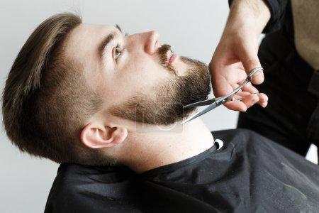 Foto de Peluquería, la barba de corte de su joven cliente guapo con las tijeras, sobre fondo blanco, en el estudio, de cerca - Imagen libre de derechos
