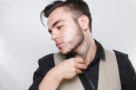Brunette barber posing with razor near his face
