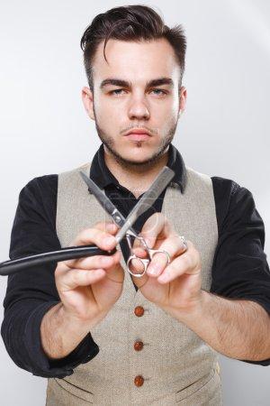 Bearded man with razor and scissors