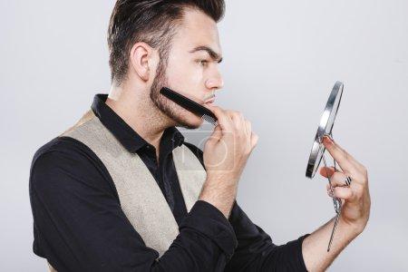 Young brutal man combing his beard