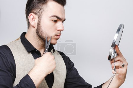 Young barber cutting his beard