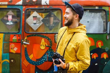 Photo for Young hipster with a beard holding oldshool film camera and looking to the side and smiling, on the background wall with patterns, wearing in bright raincoat and hat, portrait, day, outdoors, portrait in profile - Royalty Free Image