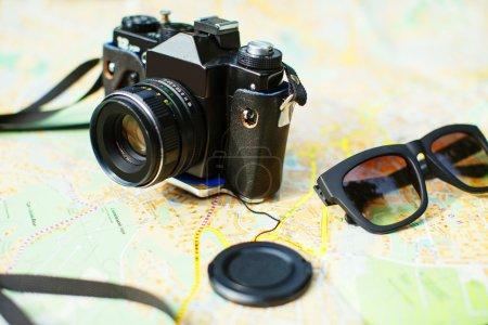 Photo pour Caméra rétro et lunettes de soleil sur la carte touristique, gros plan - image libre de droit