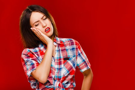 Young sad woman posing on red background