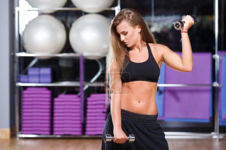 Beautiful athletic girl in gym