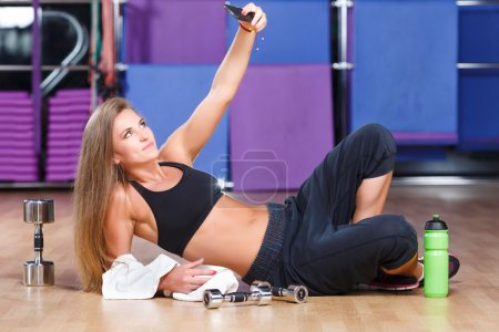 Attractive girl with phone in gym