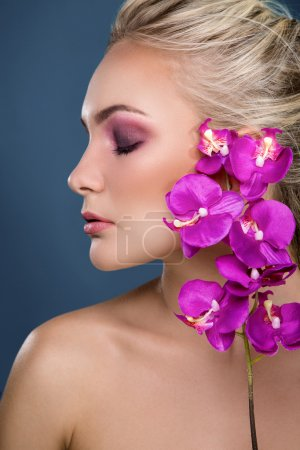 Woman with orchid near her face