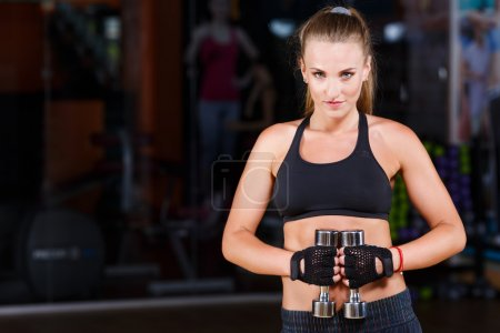 Fitness woman standing with dumbbells
