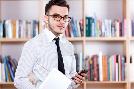 Successful young man posing with digital tablet and smart phone