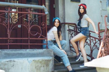 twins girls, on concrete stairs.