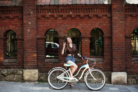 Girl with bicycle standing near wall
