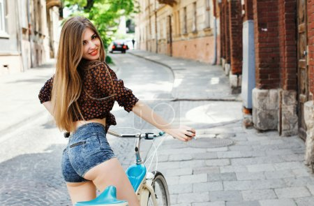 Young happy girl riding bicycle