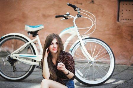 Pretty girl sitting on pavement