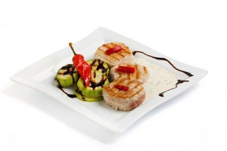 Photo pour Steak de bœuf grillé et courgettes sur une plaque blanche, fond isolé - image libre de droit