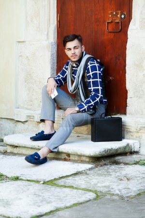 Stylish man sitting on the stairs