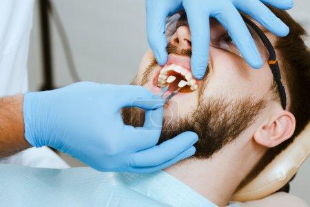 Photo pour Sélectionnez et vérifiez la couleur des dents dans la chaise du dentiste. Dentiste rend le processus de traitement de beau jeune homme . - image libre de droit