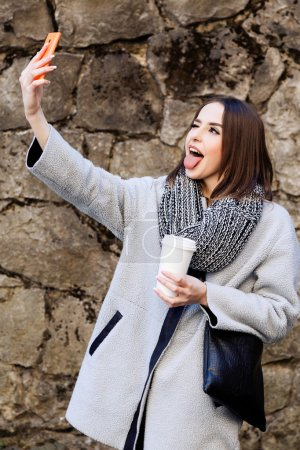Photo for Funny stylish girl, with short hair, wearing in gray jacket and scarf, taking selfie with cup of coffee on her smart phone, with stone wall on background, waist up - Royalty Free Image