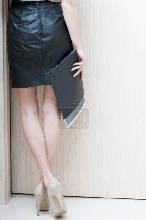 Rear view of female long legs  shod in beige shoes