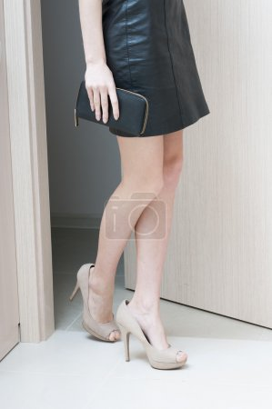 Side view of female long legs in beige shoes with high heels.