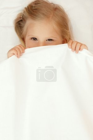 Adorable little girl under the blanket
