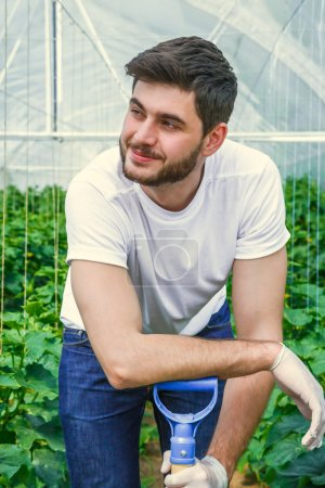 Young  sitting between rows of plants, working in a greenhouse.