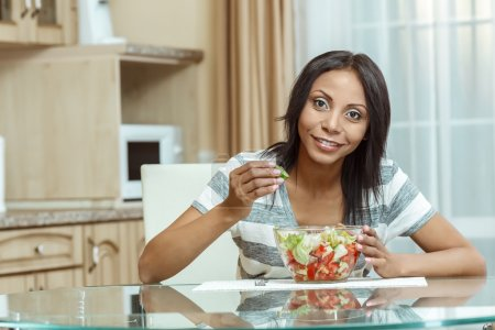 Photo for Beautiful woman eating fresh salad in modern kitchen. - Royalty Free Image