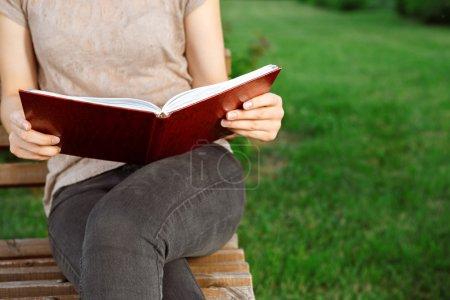 Photo pour Jolie fille avec un journal intime assis sur le banc - image libre de droit