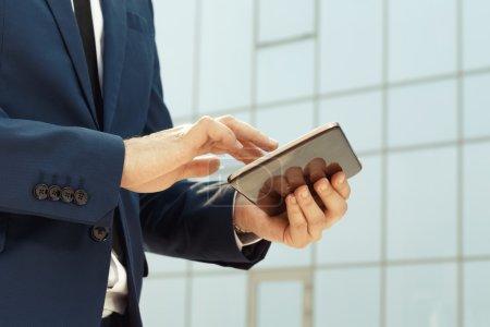 Photo pour Jeune homme d'affaires utilisant une tablette numérique à l'extérieur - image libre de droit