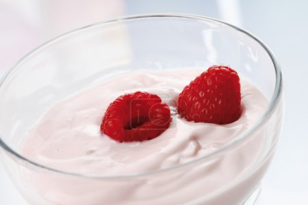 Photo for Two raspberries and yogurt in glass bowl,close up - Royalty Free Image