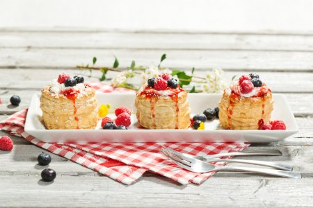 Photo for Puff pastries with vanilla-icecream and cream, blueberries and raspberries - Royalty Free Image
