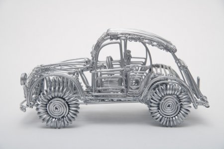 Toy car made of pliable wire against white backgro...