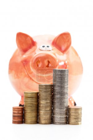 Piggy bank with piles of euro coins on white background